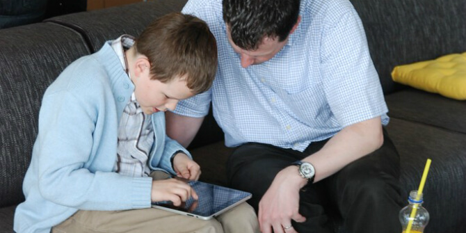 Adult and child leaning over electronic tablet device